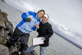 Two students holding a piece of equipment smiling for the camera with the ocean in the background