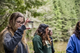 A student looking into a specimen container in the forest with other students around her