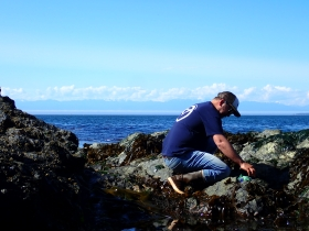 Paul Bourdeau kneeling on a large rock with bright blue background